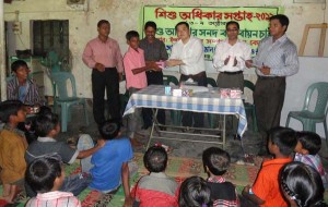 Mr Atsushi Ojima, Country Director, Shapla Neer, giving prize to the children in a prize giving ceremony organized by YPSA at Sitakund on 8 October.