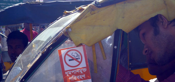 A campaigner attaching a sticker in a taxi windshield