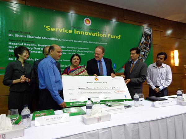 Mr. Vashkar Bhattacharjee receiving award from honorable speaker of the national parliament Dr Shirin Sharmin Chowdhury and Dan W Mozena, The Ambassador of USA in Bangladesh