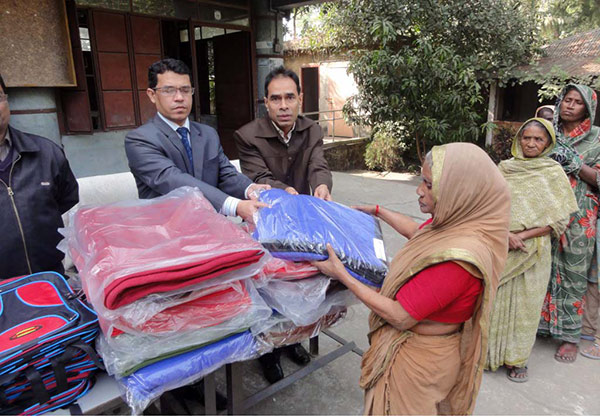 A woman from fisherman community receiving blanket