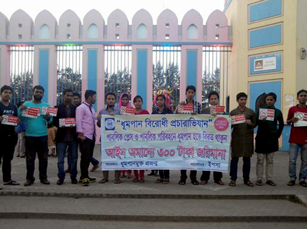 Volunteers standing with banner and sticker in front of Shadhinota park