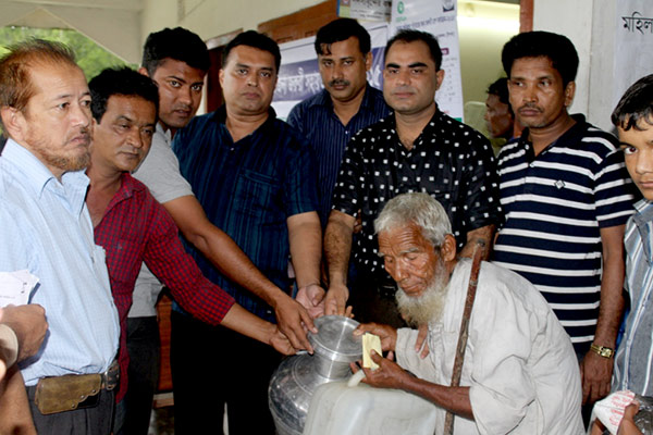 An elderly poor receiving relief goods from Md. Arifur Rahman, CE of YPSA