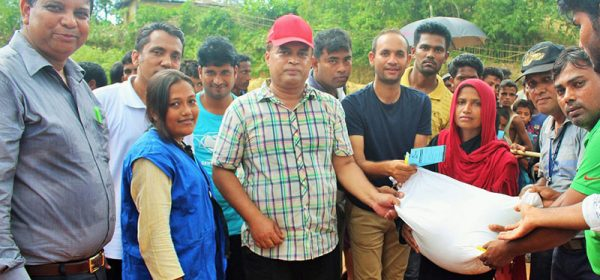 YPSA and WFP officials distributes rice bag to a female member of a Rohingya family