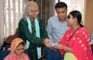 PKSF chairman handovers a phone to a woman with visually umpired student 2