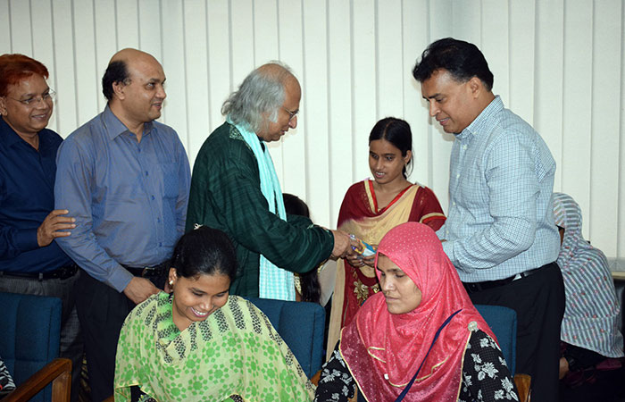 PKSF chairman handovers a phone to a woman with visually umpired student