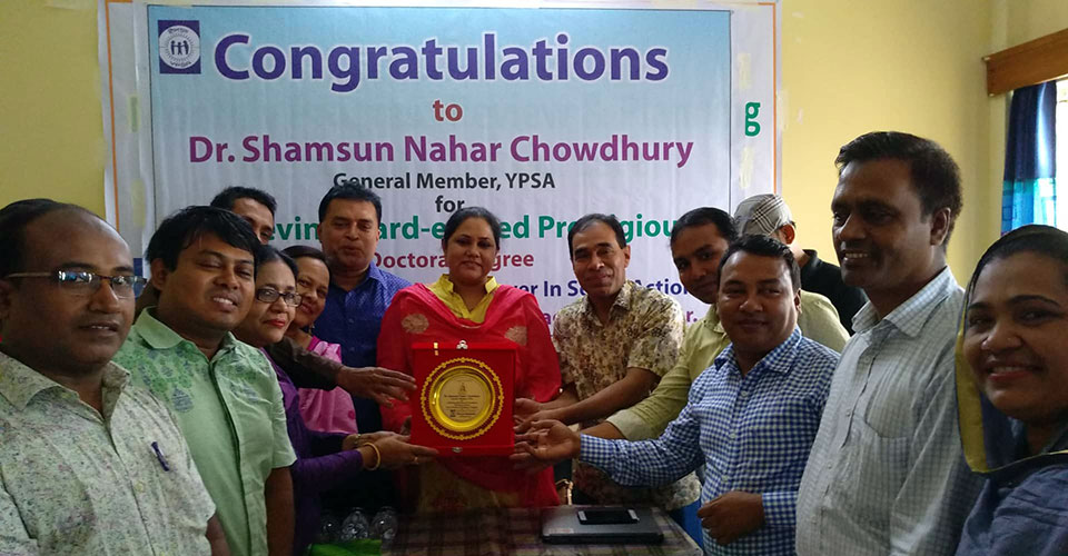 A plaque is handover to Dr. Shamsun Nahar Chowdhury