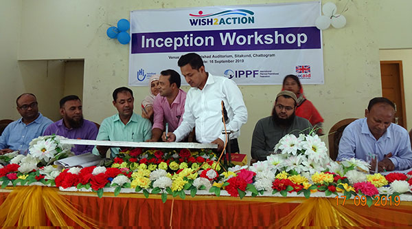 signing on a memorial board of WISH2ACTION Project