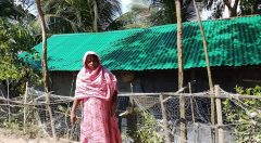 Women in front of her houses who received roof sheet from YPSA